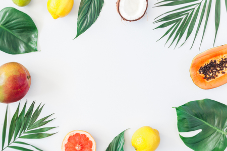 Summer tropical composition. Green palm leaves and tropical fruits on gray background. Summer concept. Flat lay, top view, copy space Stock Photo