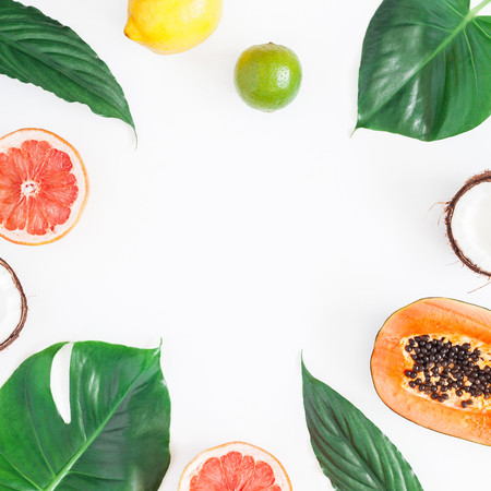 Summer tropical composition. Green palm leaves and tropical fruits on gray background. Summer concept. Flat lay, top view, copy space, square Stock Photo