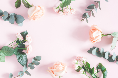 Flowers composition. Frame made of rose flowers and eucalyptus branches on pink background. Flat lay, top view, copy space