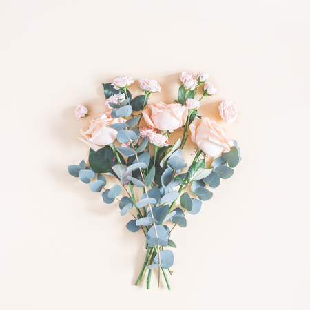 Flowers composition. Bouquet made of rose flowers and eucalyptus branches on pastel yellow background. Flat lay, top view, square 版權商用圖片