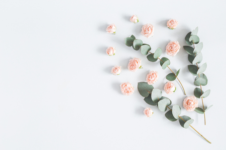Flowers composition. Frame made of rose flowers and eucalyptus branches on pastel blue background. Flat lay, top view, copy space