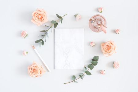 Carte d'invitation de mariage. Papier de marbre vierge, fleurs roses, branches d'eucalyptus sur fond gris. Concept de mariage. Mise à plat, vue de dessus, espace copie Banque d'images