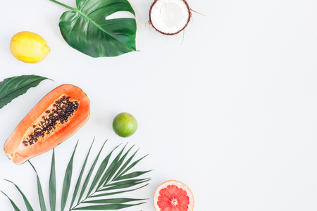 Summer tropical composition. Green palm leaves and tropical fruits on gray background. Summer concept. Flat lay, top view, copy space 版權商用圖片