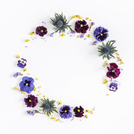Flowers composition. Wreath made of colorful pansy flowers on white background. Flat lay, top view, copy space, square
