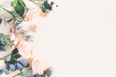 Flowers composition. Frame made of rose flowers and eucalyptus branches on pastel yellow background. Flat lay, top view, copy space