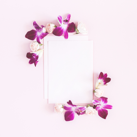 Flowers composition. Paper blank, orchid flowers on pastel pink background. Flat lay, top view, copy space, square