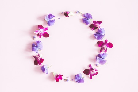 Flowers composition. Wreath made of colorful orhid flowers on pastel pink background. Flat lay, top view, copy space
