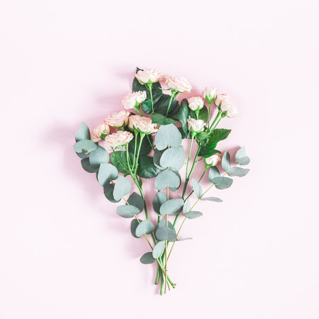 Flowers composition. Bouquet made of rose flowers and eucalyptus branches on pastel pink background. Flat lay, top view, square