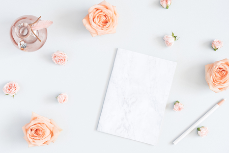 Feminine workspace with notebook, rose flowers, marble paper blank. Flat lay, top view, copy space