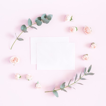 Flowers composition. Paper blank, rose flowers, eucalyptus branches on pastel pink background. Flat lay, top view, copy space 版權商用圖片