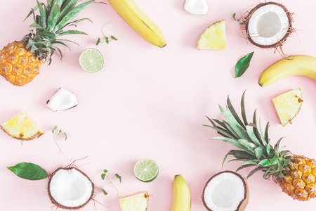 Summer fruit composition. Pineapples, coconuts, bananas on pastel pink background. Fruit background. Summer concept. Flat lay, top view, copy space 版權商用圖片