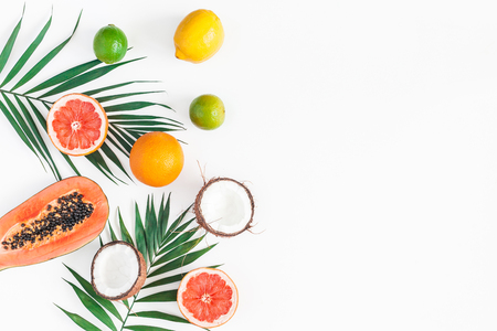 Summer tropical composition. Green palm leaves and tropical fruits on white background. Summer concept. Flat lay, top view, copy space