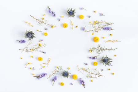 Flowers composition. Frame made of yellow and purple flowers on pastel blue background. Flat lay, top view, copy space