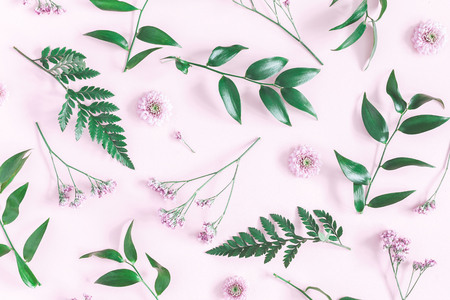 Flowers composition. Pattern made of pink flowers and green leaves on pink background. Flat lay, top view