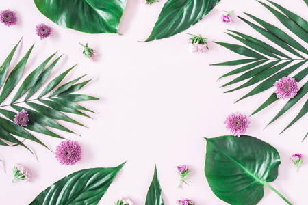 Summer flowers composition. Green tropical palm leaves and pink flowers on pastel pink background. Summer concept. Flat lay, top view, copy space