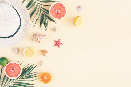 Sommerkomposition. Früchte, Hut, tropische Palmblätter, Muscheln auf pastellgelbem Hintergrund. Sommerkonzept. Flache Lage, Draufsicht, Kopierraum