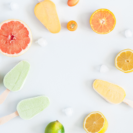 Summer background. Popsicles, colorful fresh fruits on pastel blue background. Orange, tangerine, lime, lemon, grapefruit. Summer concept. Flat lay, top view, copy space, square 写真素材