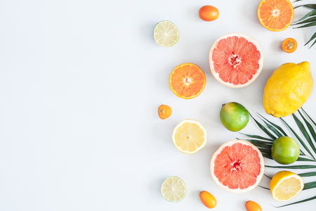 Fruit background. Colorful fresh fruits and tropical palm leaves on pastel blue background. Summer concept. Flat lay, top view, copy space 写真素材