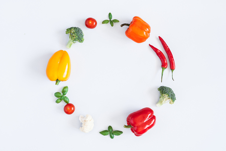 Vegetables on pastel gray background. Wreath made of fresh vegetables. Tomatoes, peppers, cabbage, green leaves. Flat lay, top view, copy space 写真素材