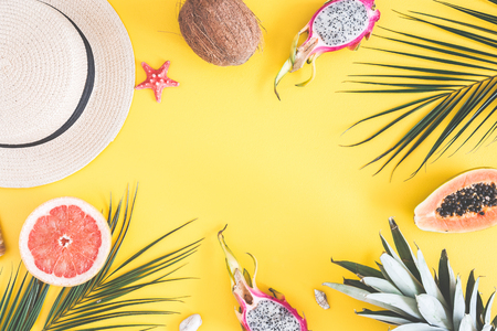 Summer composition. Tropical palm leaves, hat, pineapple, coconut, sea shells on yellow background. Summer concept. Flat lay, top view, copy space