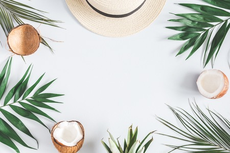 Summer composition. Tropical palm leaves, hat, coconut on pastel blue background. Summer concept. Flat lay, top view, copy space Фото со стока