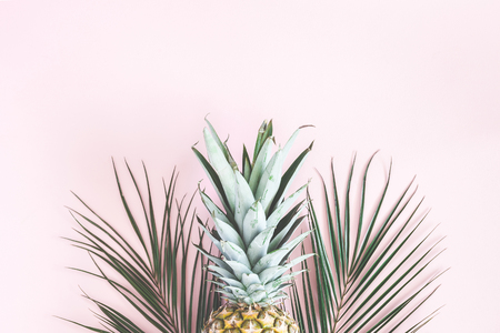 Pineapple and tropical palm leaves on pastel pink background. Summer concept. Flat lay, top view