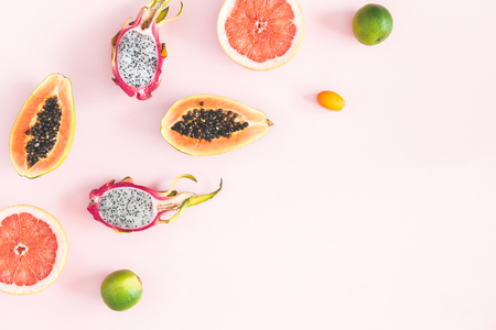 Summer fruits. Tropical pineapple, coconut, papaya, dragon fruit, orange on pastel pink background. Flat lay, top view, copy space Фото со стока
