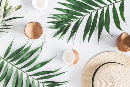 Summer composition. Tropical palm leaves, hat, coconut, pineapple on pastel blue background. Summer concept. Flat lay, top view