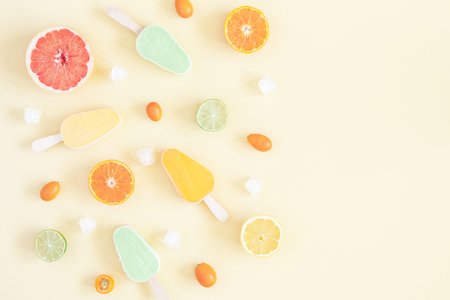 Summer background. Popsicles, colorful fresh fruits on pastel yellow background. Orange, tangerine, lime, lemon, grapefruit. Summer concept. Flat lay, top view, copy space