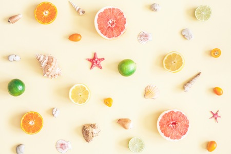 Summer pattern. Colorful fresh fruits, seashells on pastel yellow background. Summer concept. Flat lay, top view