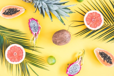 Summer fruits. Tropical palm leaves, pineapple, coconut, papaya, dragon fruit, orange on yellow background. Summer concept. Flat lay, top view