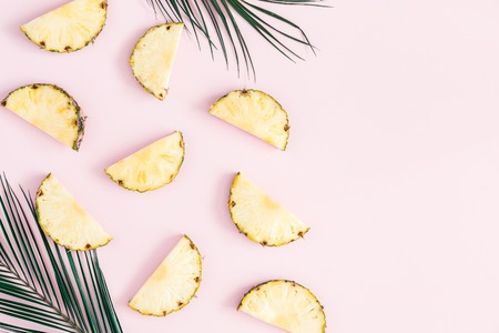 Pineapples and palm leaves on pastel pink background. Summer concept. Flat lay, top view, copy space