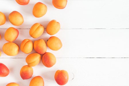 Apricots on white wooden background. Flat lay, top view, copy space Фото со стока
