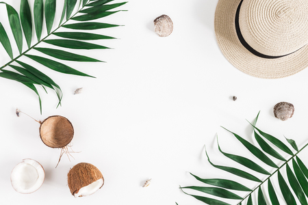 Summer composition. Tropical palm leaves, hat, coconut on white background. Summer concept. Flat lay, top view, copy space