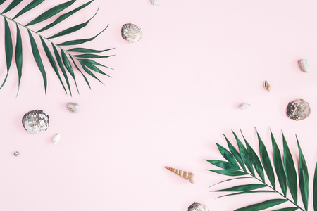 Tropical palm leaves, seashells on pastel pink background. Summer concept. Flat lay, top view, copy space Фото со стока