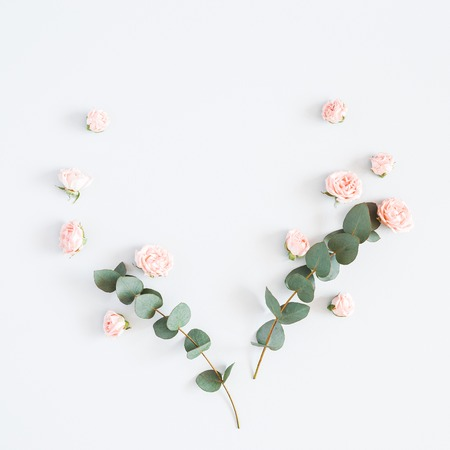 Flowers composition. Heart symbol made of rose flowers, eucalyptus branches on pastel gray background. Flat lay, top view, copy space, square