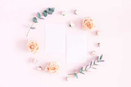 Flowers composition. Paper blank, rose flowers, eucalyptus branches on pastel pink background. Flat lay, top view, copy space Фото со стока