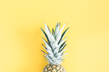 Pineapple on yellow background. Summer concept. Flat lay, top view Фото со стока