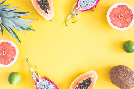 Summer fruits. Pineapple, coconut, papaya, dragon fruit, orange on yellow background. Summer concept. Flat lay, top view, copy space