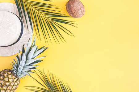 Summer composition. Tropical palm leaves, hat, pineapple, coconut on yellow background. Summer concept. Flat lay, top view, copy space Фото со стока
