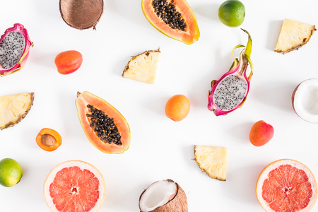 Summer fruits. Tropical pineapple, coconut, papaya, dragon fruit, orange on white background. Flat lay, top view, copy space