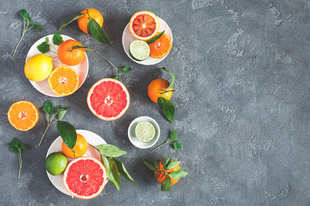 Fruit background. Colorful fresh fruits on black background. Orange, tangerine, lime, lemon, grapefruit. Flat lay, top view