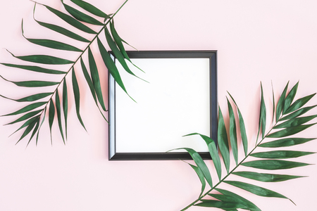 Tropical palm leaves, photo frame, on pastel pink background. Summer concept. Flat lay, top view, copy space