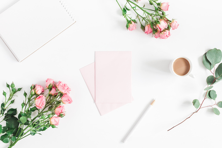 Office desk with notebook, rose flowers, eucalyptus branch, pink paper blank. Flat lay, top view, copy space