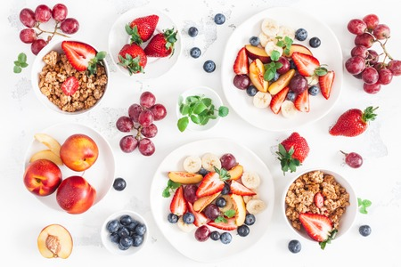 Fruit salad with strawberry, blueberry, peach, banana, grape and fresh fruits on white background. Flat lay, top view