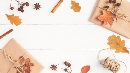 Autumn composition. Gift, autumn leaves, cinnamon sticks, anise star on wooden white background. Flat lay, top view, copy space Foto de archivo - 105196918