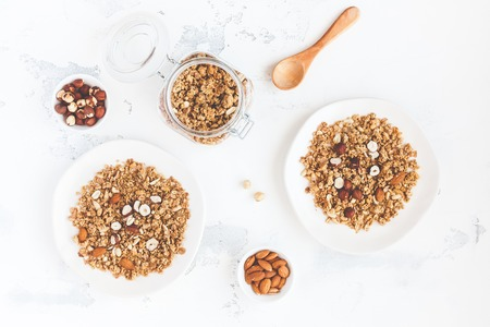 Breakfast with muesli, nuts on white background. Healthy food concept. Flat lay, top view