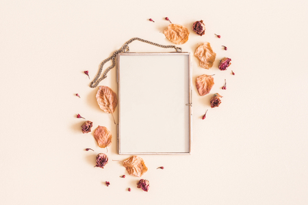 Autumn composition. Photo frame, dried flowers and leaves on pastel beige background. Autumn, fall concept. Flat lay, top view, copy space Foto de archivo - 106707411