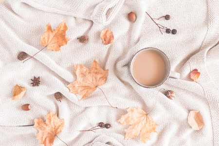 Autumn cozy composition. Cup of coffee, plaid, dried leaves. Autumn, fall concept. Flat lay, top view