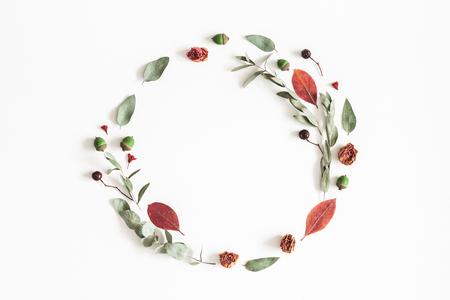 Herbstkomposition. Kranz aus Eukalyptuszweigen, Rosenblüten, getrockneten Blättern auf weißem Hintergrund. Herbst-Herbst-Konzept. Flache Lage, Draufsicht, Kopierraum